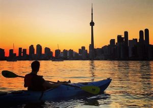Paddler sitting in kayak looking at Toronto sunset