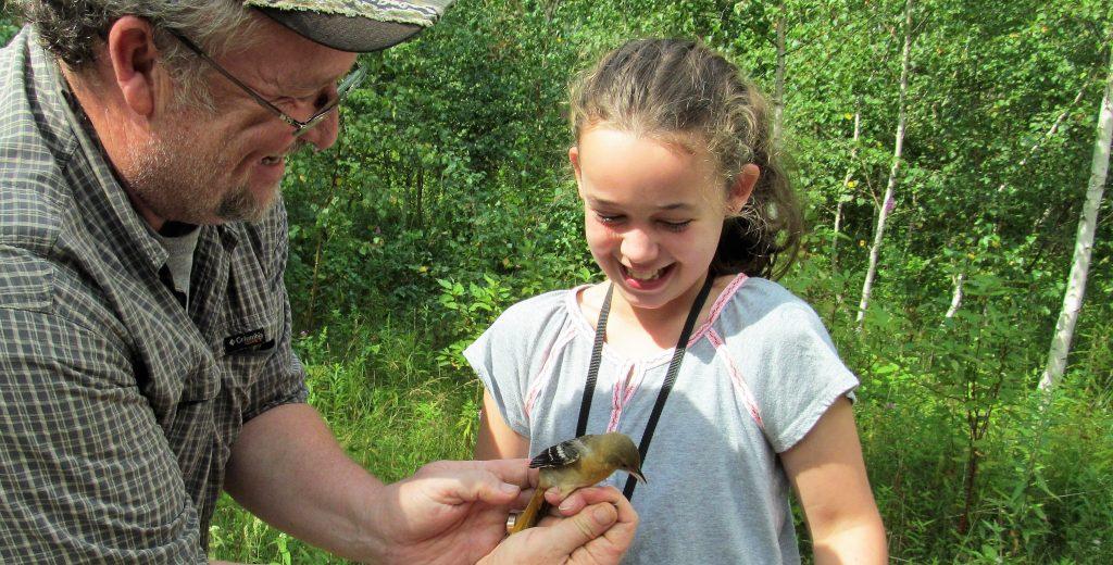 Young birder seeing a bird up close